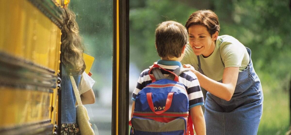 Immagine raffigurante una mamma che saluta il figlio davanti lo scuolabus